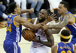 The Cleveland Cavaliers' LeBron James, middle, is hammered inside by the Golden State Warriors' Shaun Livingston, left, and Matt Barnes in the first quarter during Game 4 of the NBA Finals at Quicken Loans Arena in Cleveland on Friday, June 9, 2017. (Photo by Phil Masturzo/Akron Beacon Journal/TNS) *** Please Use Credit from Credit Field ***