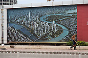 "A worker walks past a large artist's depiction of the Binhai New Development Zone's Yujiapu and Xiangluowan districts in Tianjin, China on 16 July 2013. The districts had the ambition of becoming China's newest financial center and dubbed by some ""the Manhattan of the East"",  however as the country tries to steer away from an investment driven economy, such projects are facing increasing scrutiny."