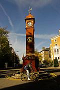 A man cycles past the famous Clock Tower at Highbury Barn, London, UK