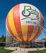 """On the 1859 Balloon Voyage at Conner Prairie Interactive History Park, visitors can ride a tethered helium balloon up to 377 feet (115 m) above the ground. The attraction is based on the historic August 17, 1859 trip of Aeronaut John Wise, where he made the first airmail delivery in the United States 25 miles (40 km) from Lafayette to Crawfordsville (Indiana) carrying 123 letters and 23 circulars. Wise was also the first to observe the jet stream, noting a """"great river of air which always blows from west to east."""" Lifted by the largest tethered gas passenger balloon in the world (105 feet or 32 m tall), the gondola can carry up to twenty people. Manufactured by the French company Aerophile, only five of these balloons exist in the United States. Conner Prairie Interactive History Park provides family-friendly fun for all ages in Fishers, Indiana, USA. Founded by pharmaceutical executive Eli Lilly in the 1930s, Conner Prairie living history museum now recreates life in Indiana in the 1800s on the White River and preserves the William Conner home (listed on the National Register of Historic Places). This image was stitched from 2 overlapping photos."""