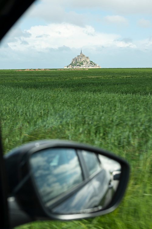 View from a moving car of the historic Mont Saint-Michel, topped with its medieval abbey, in Lower Normandy, France.