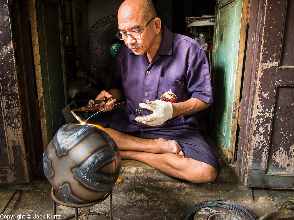 """19 AUGUST 2013 - BANGKOK, THAILAND:     A craftsman solders the seams on a monk's bowl, called """"bat"""" (pronounced with a long """"a"""" as in baat) on Soi Baan Bat in Bangkok. The bowls are made from eight separate pieces of metal said to represent the Buddha's Eightfold Path. The Monk's Bowl Village on Soi Ban Baat in Bangkok is the only surviving one of what were originally three artisan's communities established by Thai King Rama I for the purpose of handcrafting """"baat"""" the ceremonial bowls used by monks as they collect their morning alms. Most monks now use cheaper factory made bowls and the old tradition is dying out. Only six or seven families on Soi Ban Baat still make the bowls by hand. Most of the bowls are now sold to tourists who find their way to hidden alleys in old Bangkok. The small family workshops are only a part of the """"Monk's Bowl Village."""" It is also a thriving residential community of narrow alleyways and sidewalks.  PHOTO BY JACK KURTZ"""