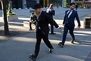 Members of a dance group perform a routine on rollerskates in the City of London, England, United Kingdom. Smartly dressed in suits and one in a bowler hat, the dancers performed their moves for a video being shot in the shadow of the Lloyds Building and the Leadenhall Building.