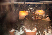 Candles burning on deck in winter artistically surrounded by evergreen bows and snow. St Paul Minnesota USA