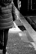 Child clutches her mask as she walks through the rainy streets of Hove, UK, during England's second wave of COVID-19 cases on 19 December 2020.