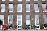 In de nieuwbouwwijk IJburg bij Amsterdam staan fietsen voor de huizen opgesteld, waaronder de enkele bakfiets.<br /> <br /> Bikes, amongst others cargobikes, are parked in front of the houses at the new neighborhood IJburg in Amsterdam