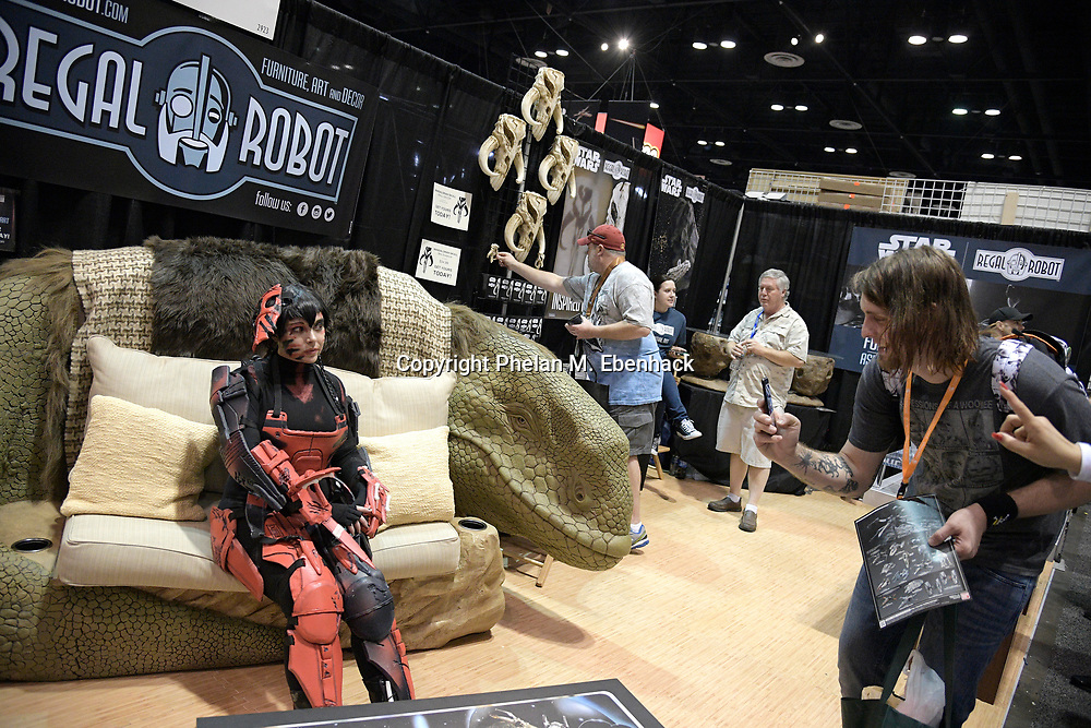 Peter Viox, right, of Lexington, Ky., photographs Eden Grey on a movie-themed chair during the Star Wars Celebration event in Orlando, Fla., Friday, April 14, 2017. (Photo by Phelan M. Ebenhack)