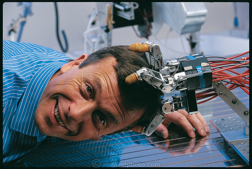 """Once intelligent robots are created, argues Kevin Warwick, (seen here clowning with a lab robot hand), of the University of Reading in the UK, it will not take them long to realize their superiority to flesh-and-blood beings. """"The human race as we know it,"""" he has written, """"is very likely in its endgame"""" machines will wipe us out. Believing that this dreadful scenario is unavoidable, Warwick nevertheless continues his research into robotics. From the book Robo sapiens: Evolution of a New Species, page 29."""