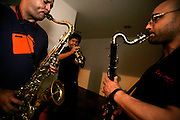 """Three members of """"Jazz ao Centro Orchestra"""" practising before an orchestra rehearsal."""