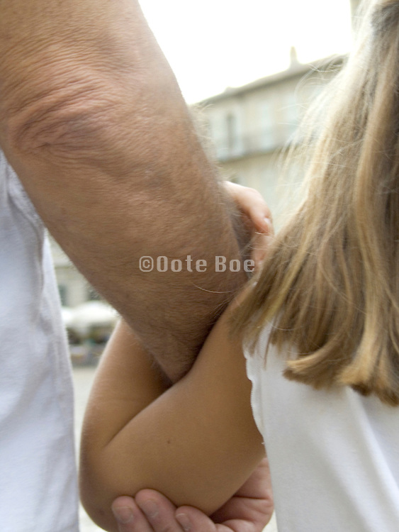 a child holding her father by the arm