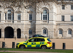 © Licensed to London News Pictures. 27/03/2020. London, UK. An ambulance car stops in Horse Guards Road near the back of Downing Street as Prime Minister Boris Johnson and Health Secretary Matt Hancock reveal they have contracted coronavirus and are in self-isolation as the coronavirus crisis continues. Photo credit: Alex Lentati/LNP