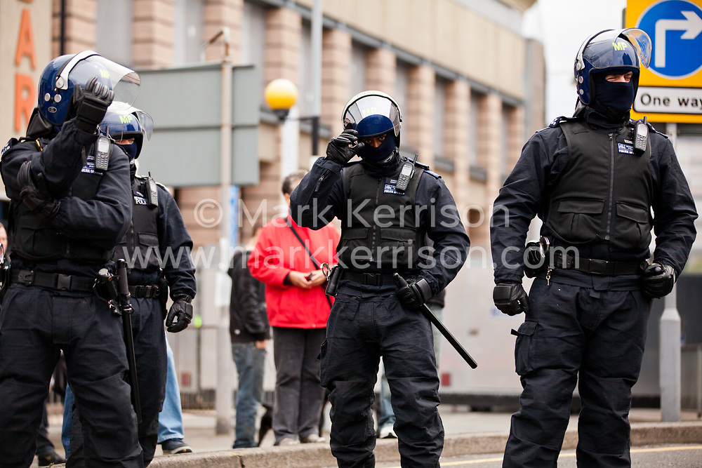 Luton, UK. 5th May, 2012. Riot police officers stand in front of a steel barrier deployed to separate supporters of Unite Against Fascism attending the We Are Luton/Stop The EDL march from supporters of the far-right English Defence League. Around 1,500 police were deployed in Luton for the rival marches from twenty forces around the UK.