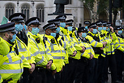 Metropolitan police wearing face masks form a cordon at Extinction Rebellion demonstration on 3rd September 2020 in London, United Kingdom. With government resitting after summer recess, the climate action group has organised two weeks of events, protest and disruption across the capital. Extinction Rebellion is a climate change group started in 2018 and has gained a huge following of people committed to peaceful protests. These protests are highlighting that the government is not doing enough to avoid catastrophic climate change and to demand the government take radical action to save the planet.