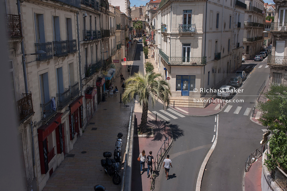 Aerial view of apartments, parked cars and pedestrians on Rue A. Ollivier in Montpellier, south of France.