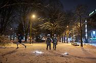 Tartu, Estonia - February 27, 2020:A man jogs past two nude statues in Tartu Keskpark on a snowy winter night in Tartu, Estonia.