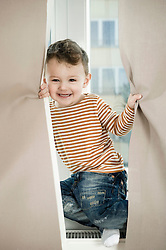 Portrait of boy playing with curtain, smiling