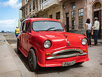 Three people looking and talking, by the red Standard 10 automobile in Havana.