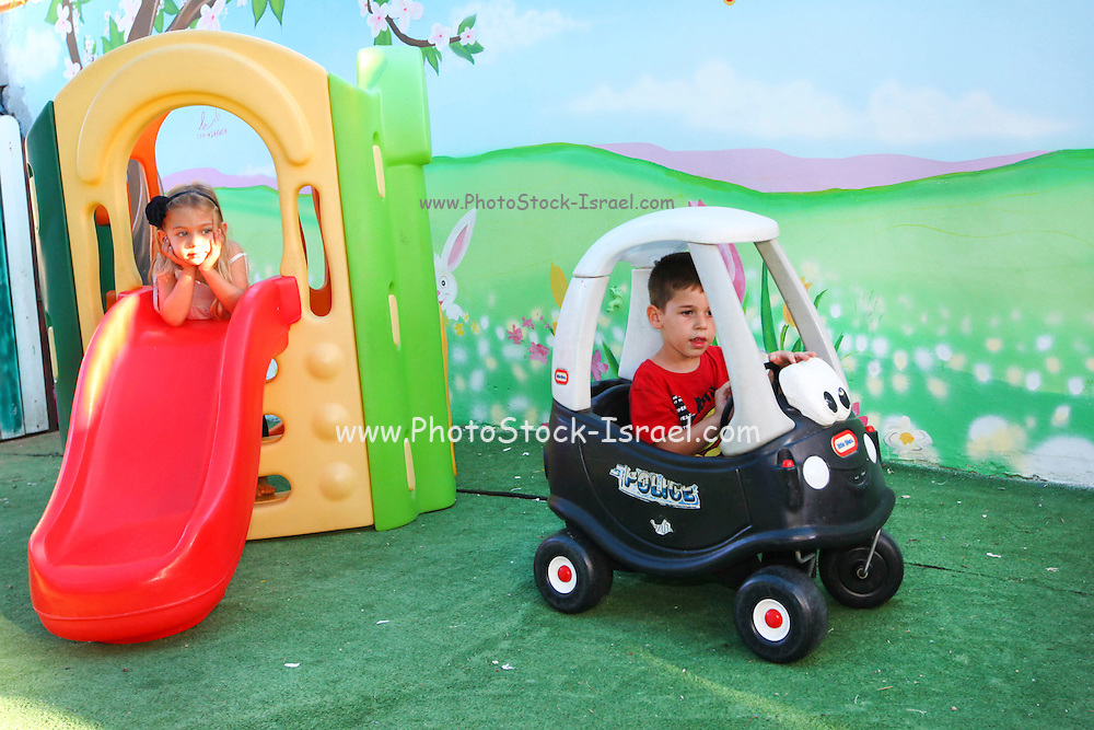 Young girl and boy play in a kindergarten playroom