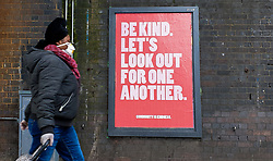 © Licensed to London News Pictures. 30/03/2020. London, UK. A woman wearing a face mask walks past a 'Be Kind. Let's Look out for one Another.' sign in north London as  coronavirus lockdown continues.  Photo credit: Dinendra Haria/LNP