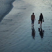 Couple walking at sunset on the beach.<br /> Santa Barbara, CA.