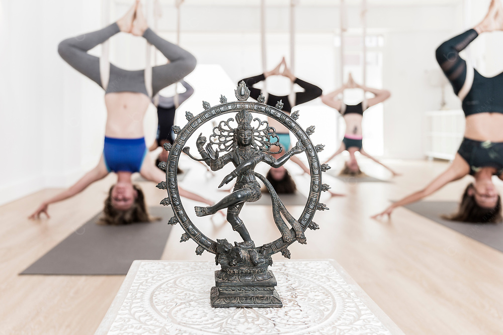 Women doing aerial yoga exercises In front old statue of hindu god