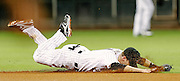 Sept 12, 2012; Houston, TX, USA; Houston Astros shortstop Jed Lowrie (4) dives for a ground ball against the Chicago Cubs during the fourth inning at Minute Maid Park. Mandatory Credit: Thomas Campbell-US PRESSWIRE