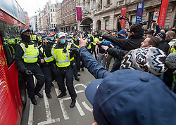 © Licensed to London News Pictures. 20/03/2021. London, UK. Police officers draw batons as they clash with with protesters on Piccadilly, during a Rally for Freedom in central London, to protest against the continued lockdown restrictions imposed to fight the spread of coronavirus. Similar events are taking place at cities around the world. Photo credit: Ben Cawthra/LNP
