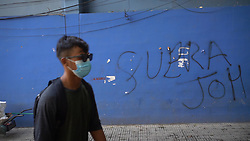 A man wearing a facemask walks past a wall painted with the phrase Fuera JOH - calling for the end of the presidency of Juan Orlando Hernandez in Honduras.