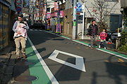 Father carrying a baby in a sling. Suburban street in the Seta District of Setagaya Ward, Tokyo.