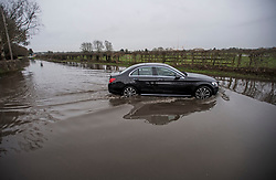 © Licensed to London News Pictures. 03/02/2021. Old Windsor, UK. A car attempts to pass through flood water which has closed the Windsor Road between Windsor and Staines, where the River Thames has broken it's banks. Large parts of the UK experience more wet conditions which is expected to bring further flooding. Photo credit: Ben Cawthra/LNP