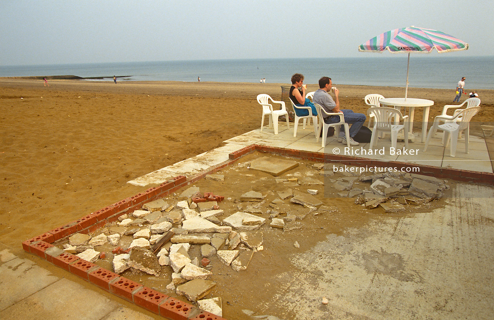 Sitting on garden seats, a seaside couple enjoy ice creams near broken building materials in the resort of Sandown. A decaying pile of rubble and building bricks have been left on the ground where visitors and tourists sit on their holiday making for a grim and depressing experience and dystopic landscape. This is the seaside resort of Sandown on the Isle of Wight, twinned (jumelée in French) with the town of Tonnay-Charente, in the western French département of Charente-Maritime. Its American twin town is St. Pete Beach, Florida.