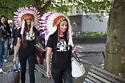 Two women wearing Native American headdresses on the riverside walkway. The South Bank is a significant arts and entertainment district, and home to an endless list of activities for Londoners, visitors and tourists alike.