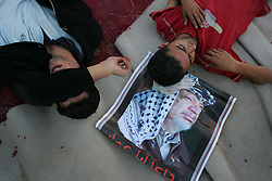 Palestinians collapse after the body of leader Yasser Arafat is laid to rest at his compound, Ramallah, Palestinian Territories, Nov. 12, 2004. Arafat died in a Paris hospital at the age of 75.