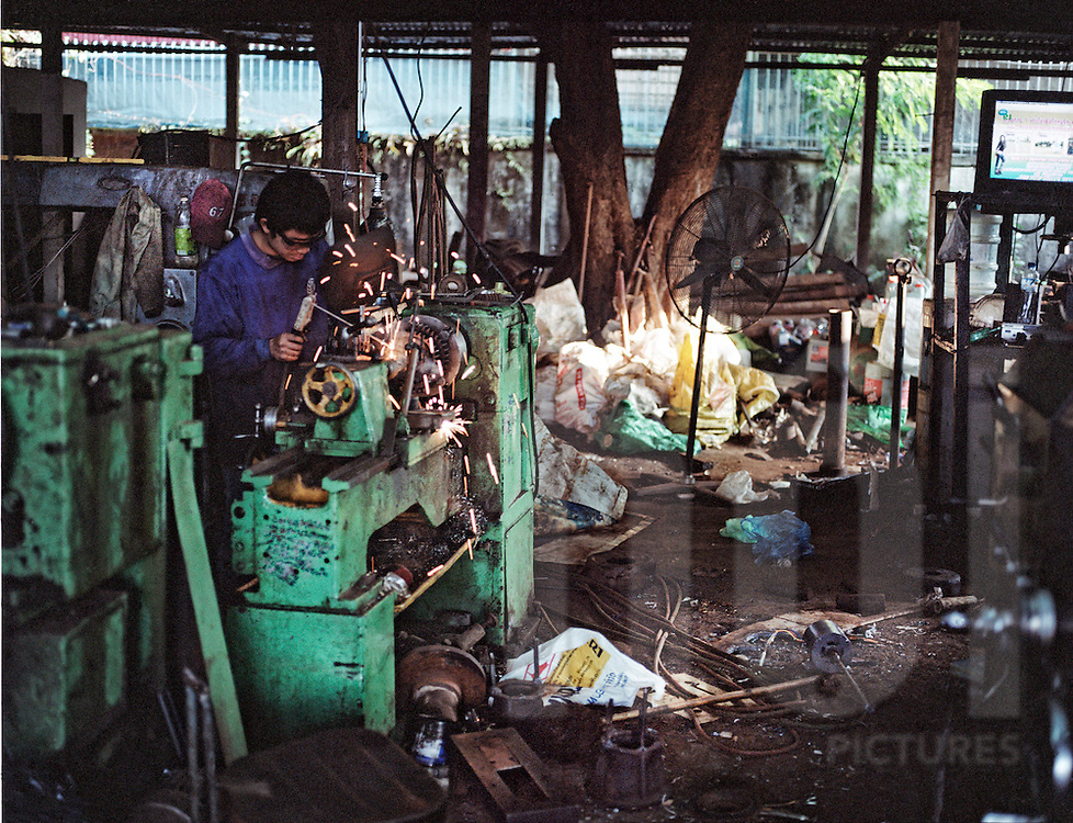 A Lao man welds in a messy workshop recycling iron, Thalhek, Laos, Asia