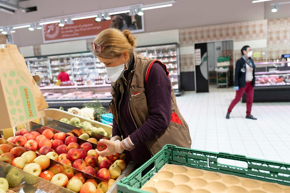 L'Intermarché de La Loupe, le 18 mars 2020. Une employée du supermarché, protégée par un masque et des gants,  remplit un étalage de pommes au rayon Fruits et Légumes.<br /> Intermarché de La Loupe, March 18, 2020. A supermarket employee, protected by a mask and gloves, fills a display of apples in the Fruits and Vegetables department.