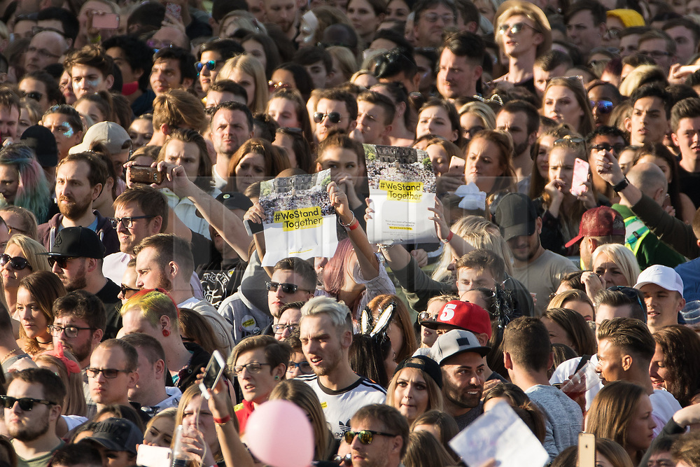 """© Licensed to London News Pictures . 04/06/2017 . Manchester , UK . People hold """" We stand together """" posters in the crowd . The One Love Manchester benefit concert for victims of the Manchester Arena terrorist attack , at the Emirates Old Trafford Cricket Stadium . Ariana Grande, Justin Bieber, Coldplay, Katy Perry, Miley Cyrus, Pharrell Williams, Usher, Take That, Robbie Williams, Black Eyed Peas and Niall Horan are amongst the performers. Photo credit : Joel Goodman/LNP"""
