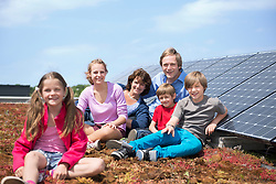 Father mother kids sitting solar park