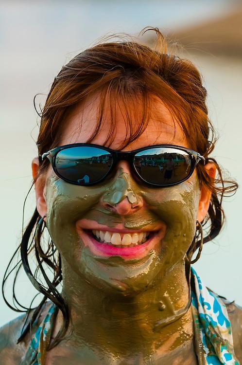 Woman slathered in Dead Sea mud enjoying the waters of the Dead Sea at the Leonardo Plaza Dead Sea Hotel, Israel.