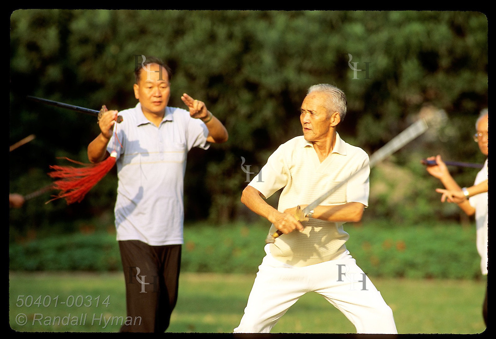 Older man practices sword play among friends at sunrise in Jin An Park in central Shanghai. China