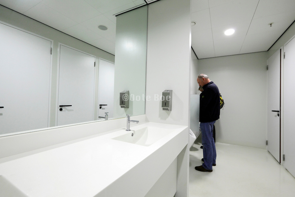 clean male public toilette room with sink