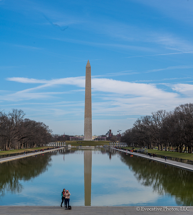 Washington DC, USA — February 3, 2020.  A photo the Washington Memorial that includes tourists posing for a selfie by the reflecting pool.