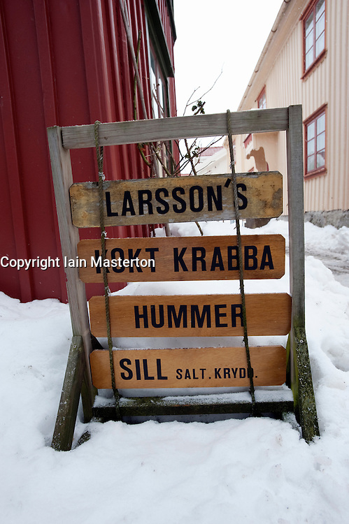 Sign outside fish shop in traditional fishing village Mollosund during winter after snow on Bohuslan coast in Sweden