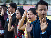 04 JULY 2019  - DES MOINES, IOWA: People being naturalized American citizens take the Oath of Citizenship before the Iowa Cubs game. Thirty people became US citizens during a naturalization ceremony at the Iowa Cubs game in Des Moines. The naturalization ceremony is an Iowa Cubs 4th of July tradition. This is the 11th year they've held the ceremony.         PHOTO BY JACK KURTZ