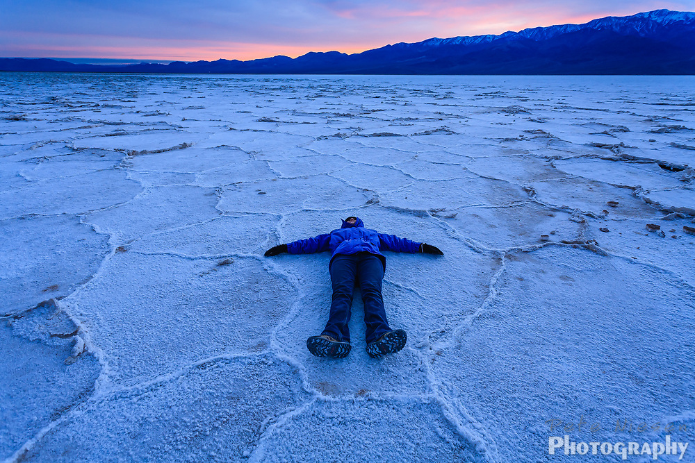 Hiker lays on the salt flats near Bad Water Basin in Death Valley at sunset