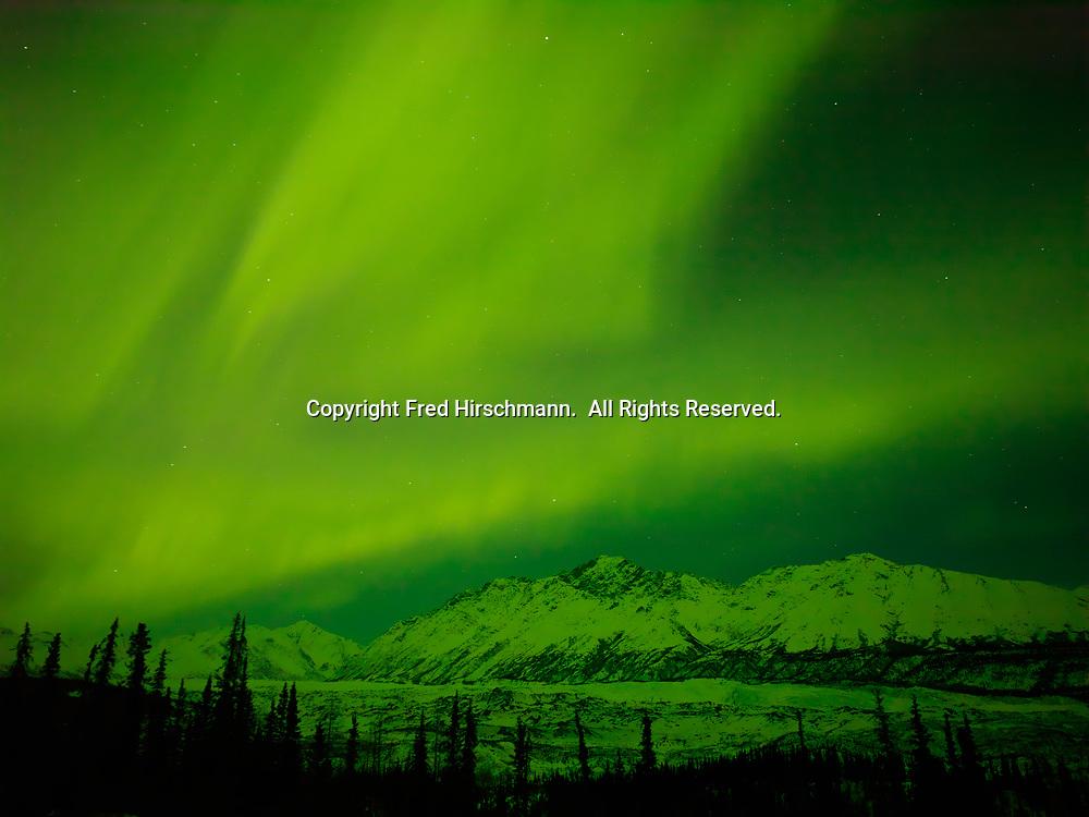 Green aurora borealis illumintating the Matanuska Glacier and Mount Wickersham of the Chugach Mountains, night of March 16-17, 2013, Alaska.