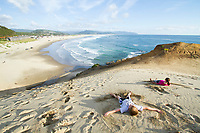 Kids playing on sand dune in Pacific City, OR Model released.