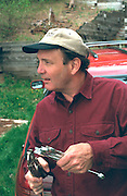 Man age 55 holding wrenches near Roy Lake.  Nisswa  Minnesota USA