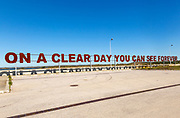 Large red rusty capital letters ON A CLEAR DAY YOU CAN SEE FOREVER blue sky background, Alqueva dam, Moura, Portugal