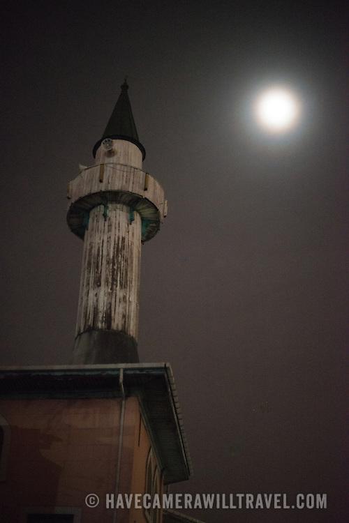 The moon shines through light mist onto a tower in Karakoy, Istanbul.
