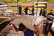 Colombia, Puerto Nariño, 2010. Puerto Nariño. <br /> Un hombre descarga mercancías en el puerto secundario del Amazonas colombiano. El poblado recibe el nombre de Puerto Nariño por una embarcación de carga, el Vapor Nariño, que encalló en estas aguas a principios del siglo XX. Actualmente, narcotraficantes y guerrilleros se disputan el poder en este territorio, que forma parte de la ruta de la cocaína en esta zona de América Latina. La presencia de policías y militares se volvió constante en los últimos años.<br /> A man unloads his merchandise at a secondary port on the Colombian Amazon. The town is called Port Nariño by a boat, the Nariño Steam, which ran aground in these waters at the beginning of the 20th century.  Currently, drug traffickers and guerrillas compete for power in this territory, which is part of the route used for cocaine trafficking in this part of Latin America. The presence of police and the military has become constant in the last years.